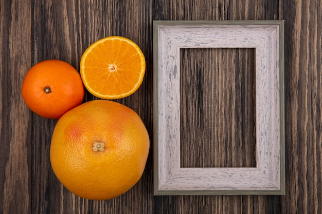 Vue de dessus de l'espace de copie de pamplemousse avec des oranges et un cadre gris sur fond de bois