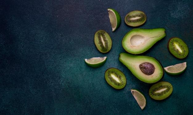 Vue de dessus espace copie tranches de kiwi moitiés d'avocat et tranches de citron vert sur fond vert foncé