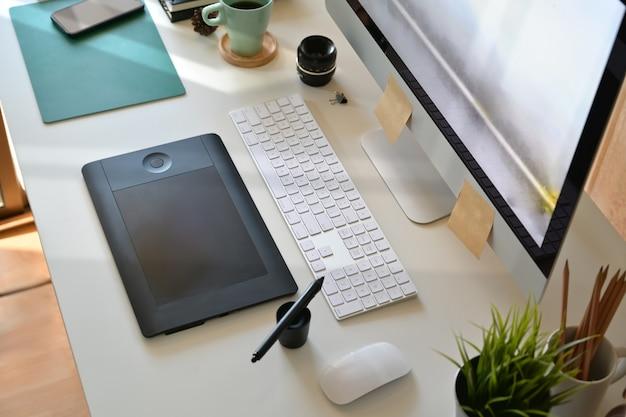 Vue de dessus, espace de travail d'artiste designer, ordinateur, tablette de dessin numérique et fournitures créatives