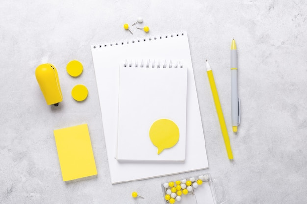 Vue de dessus de l'espace de travail avec bloc-notes et accessoires de papeterie sur fond de pierre grise. illuminating yellow et ultimate grey, couleurs de l'année 2021 - image
