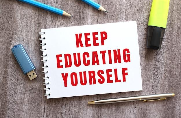 Vue de dessus de l'espace de travail. bloc-notes avec du texte continuez à vous éduquer, un stylo, des crayons, une clé usb sur une table en bois grise. concept d'entreprise.