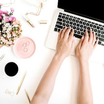 Vue de dessus de l'espace de travail de bureau avec les mains tapant sur un ordinateur portable