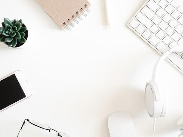 Vue de dessus de l'espace de travail de bureau avec ordinateur portable, smartphone et gadget sur fond blanc