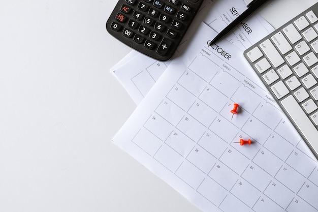 Vue de dessus de l'espace de travail de bureau avec tasse à café, clavier et horaire de travail sur fond de tableau blanc. pose à plat