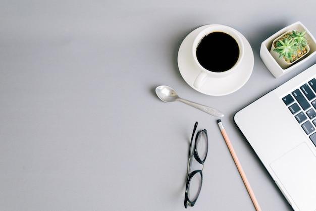 Vue de dessus de l'espace de travail avec café et ordinateur.