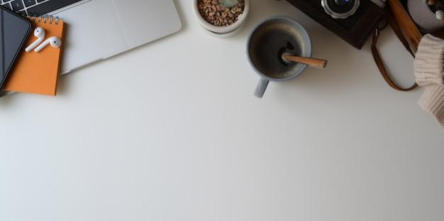 Vue de dessus d'un espace de travail confortable avec ordinateur portable et fournitures de bureau sur fond de bureau blanc