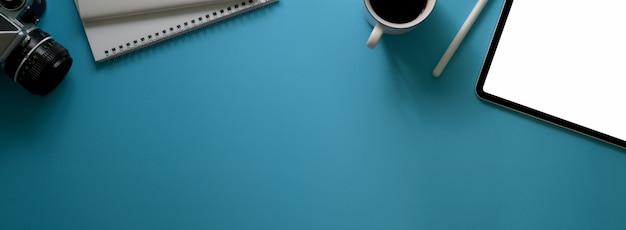 Vue de dessus de l'espace de travail créatif avec tablette à écran vide, tasse à café, cahiers de journal, appareil photo et espace de copie