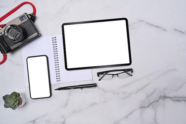 Vue de dessus de l'espace de travail du photographe avec tablette, smartphone, appareil photo et ordinateur portable