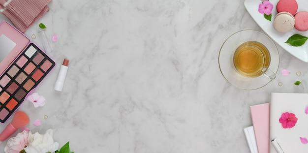 Vue de dessus de l'espace de travail féminin rose doux avec espace de copie et maquillage sur le bureau en marbre