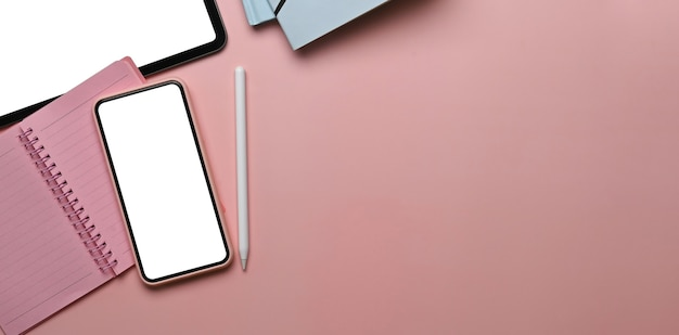 Vue de dessus de l'espace de travail féminin avec téléphone intelligent, tablette numérique, ordinateur portable et espace de copie sur table rose.