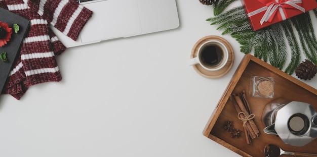 Vue de dessus de l'espace de travail de noël avec ordinateur portable, tasse à café et présent sur un bureau en bois vintage