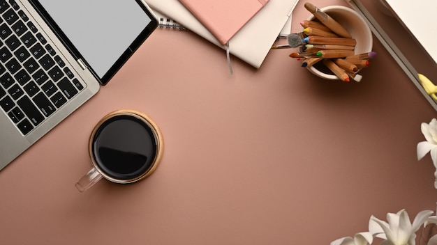 Vue de dessus de l'espace de travail avec ordinateur portable, tasse à café, papeterie et espace copie sur la table