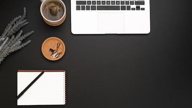 Vue de dessus de l'espace de travail avec ordinateur portable et tasse de thé