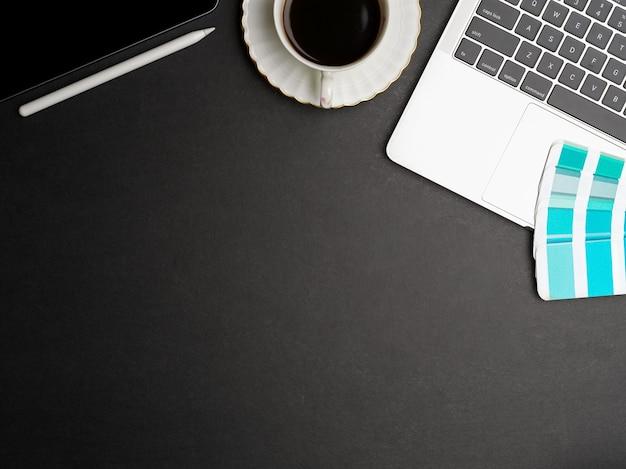 Vue de dessus espace de travail plat créatif avec ordinateur portable, fournitures, tasse à café et espace de copie sur un bureau noir