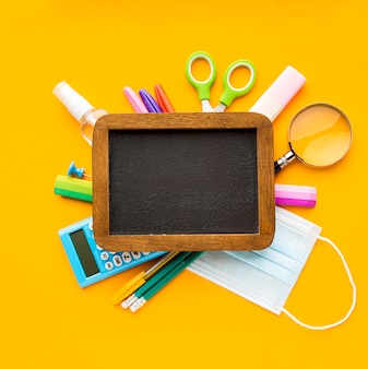 Vue de dessus des essentiels de la rentrée scolaire avec tableau noir et crayons