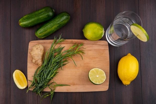 Vue de dessus de l'estragon sur une planche de cuisine en bois avec concombre citrons sur surface en bois