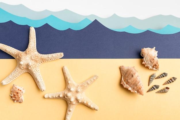 Vue de dessus des étoiles de mer et des coquillages avec des vagues de l'océan en papier