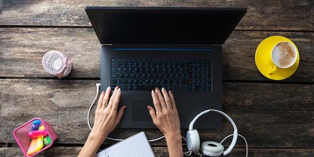 Vue de dessus d'une étudiante travaillant sur un ordinateur portable avec des écouteurs, des marqueurs colorés et une tasse de café à côté sur la table.
