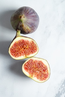 Vue de dessus exotique frais coupé sur demi figue sur table en marbre. mur photo alimentaire. schéma créatif de figues entières et tranchées. mise à plat. vue d'en-haut.