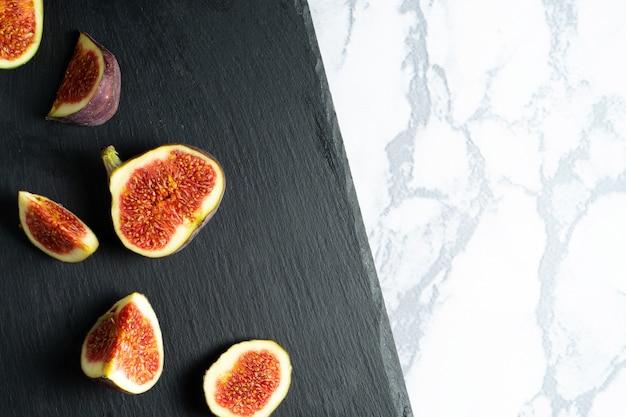 Vue de dessus exotique frais coupé sur la moitié de figue sur une planche en pierre noire sur une table en marbre. mur photo alimentaire. schéma créatif de figues entières et tranchées. mise à plat. vue d'en-haut. délicieux fruits d'été