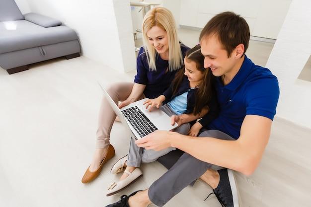 Vue de dessus de la famille assise sur le sol à l'aide d'un ordinateur portable dans sa chambre à la maison