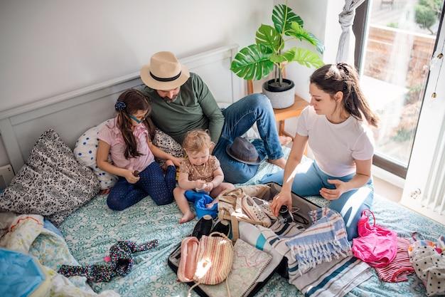 Une vue de dessus d'une famille avec deux petites filles emballant pour des vacances au lit à la maison.