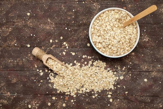Vue de dessus de la farine d'avoine crue à l'intérieur de la plaque blanche sur brun, petit-déjeuner de santé crue alimentaire