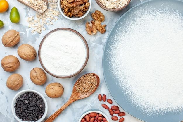 Vue de dessus de la farine blanche à l'intérieur de l'assiette avec des graines de noix et des œufs sur de la pâte de noix blanche cuire au four photo couleur gelée de gâteau aux fruits