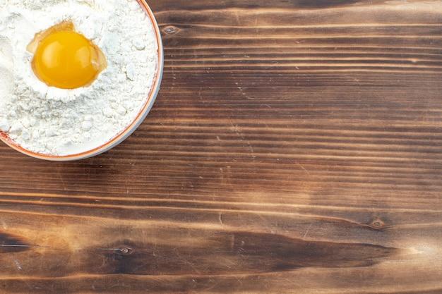 Vue de dessus farine blanche avec oeuf à l'intérieur de la plaque sur fond marron