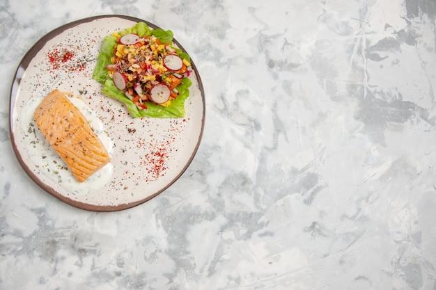 Vue de dessus de la farine de poisson et de la délicieuse salade sur une assiette sur une surface blanche tachée