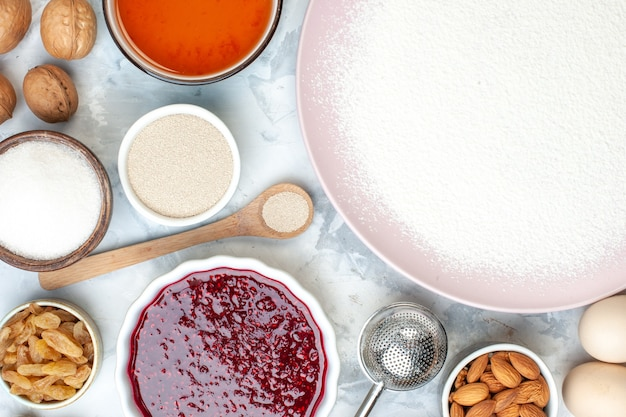 Vue de dessus farine en poudre sur assiette bols avec graines de sésame amandes confiture oeufs cuillère en bois sur table