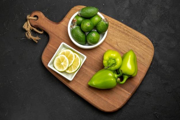 Vue de dessus de la feijoa fraîche avec du poivron vert et du citron sur la surface sombre de la farine de plantes d'agrumes de fruits