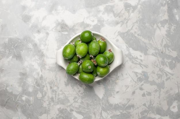 Vue de dessus feijoa vert frais à l'intérieur de la plaque sur la surface blanche des plantes d'arbres fruitiers fraîcheur couleur exotique douce