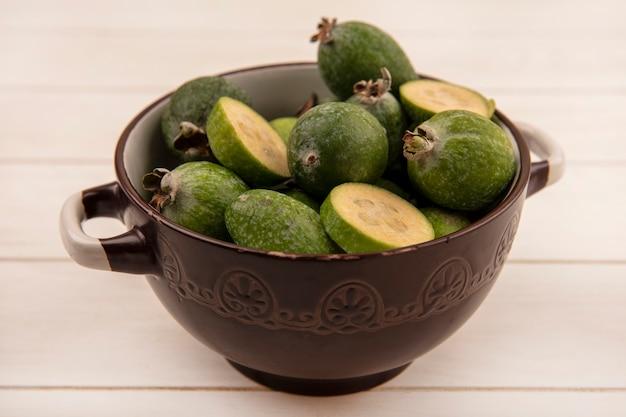 Vue de dessus de feijoa vert sain sur un bol sur une surface en bois blanche