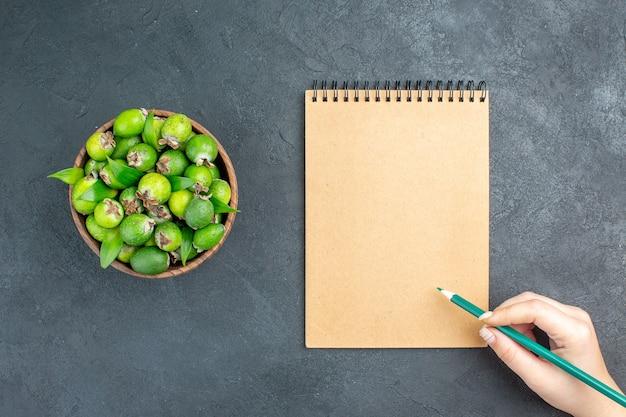 Vue de dessus feijoas frais dans le bloc-notes seau crayon vert dans la main de la femme sur une surface sombre