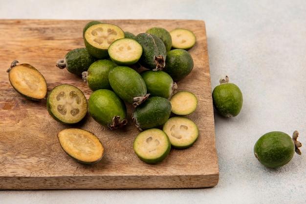 Vue de dessus de feijoas frais entiers et coupés en deux, isolés sur une planche de cuisine en bois sur fond gris