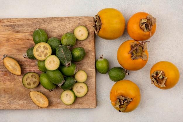 Vue de dessus de feijoas frais entiers et coupés en deux isolés sur une planche de cuisine en bois avec des kakis sur un mur gris
