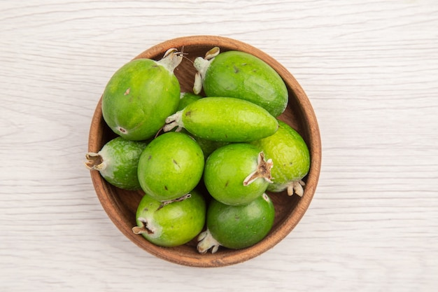 Vue de dessus des feijoas frais à l'intérieur de la plaque sur fond blanc couleur fruit exotique régime mûr exotique