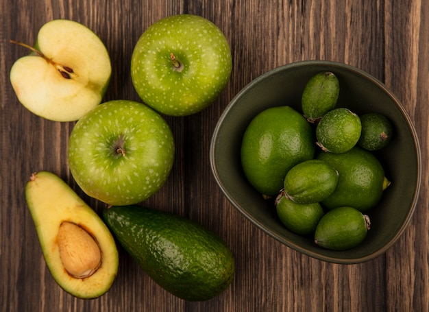 Vue de dessus de feijoas frais avec des limes sur un bol avec des pommes vertes et des avocats isolés sur une surface en bois