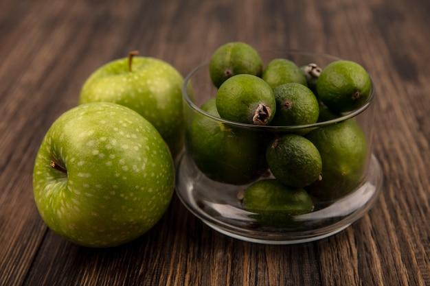 Vue de dessus de feijoas mûres fraîches sur un bol en verre avec des pommes vertes isolé sur un mur en bois