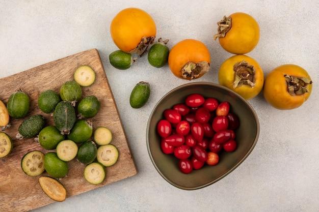 Vue de dessus de feijoas mûrs entiers et coupés en deux isolés sur une planche de cuisine en bois avec des kakis et des cerises cornaline sur un bol sur une surface grise