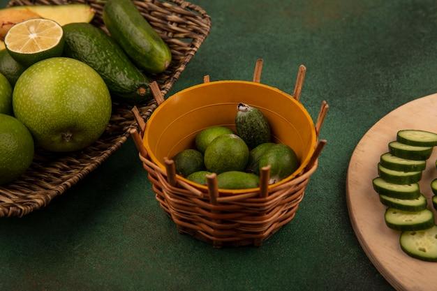 Vue de dessus des feijoas sur un seau avec des tranches de concombre hachées sur une planche de cuisine en bois avec des pommes vertes avocat concombre sur un plateau en osier sur fond vert