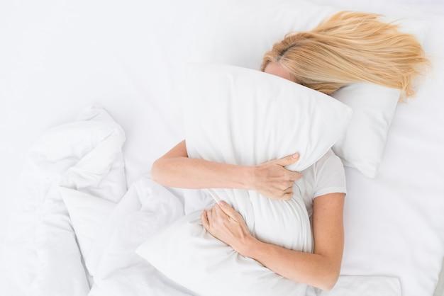 Vue de dessus femme adulte tenant un oreiller