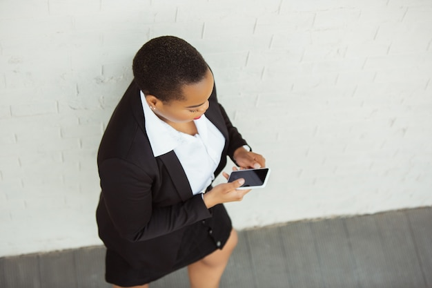 Vue de dessus d'une femme d'affaires afro-américaine en tenue de bureau faisant défiler le téléphone