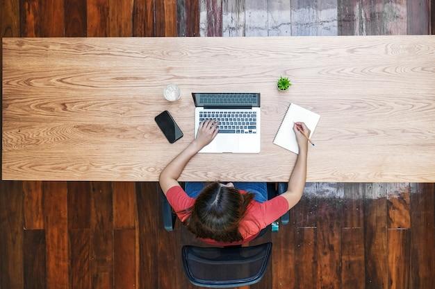 Vue de dessus d'une femme d'affaires asiatique utilisant un ordinateur portable technologique et un cahier d'écriture pour travailler