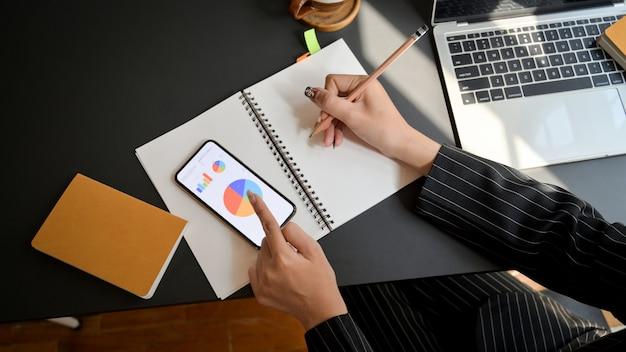 Vue de dessus de femme d'affaires écrit sur un ordinateur portable tout en regardant le tableau des affaires dans un lieu de travail confortable