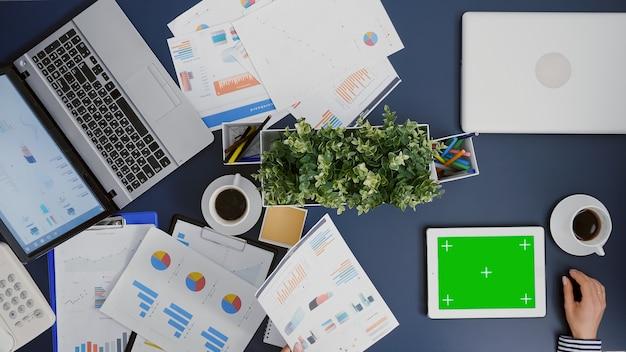 Vue de dessus d'une femme d'affaires regardant une maquette de tablette à clé chroma à écran vert
