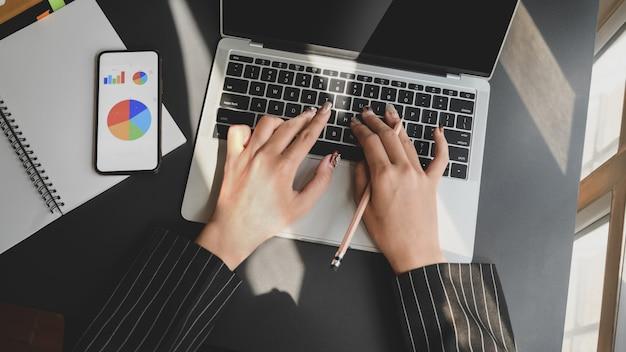 Vue de dessus de femme d'affaires travaillant sur ordinateur portable tout en regardant le tableau des affaires sur smartphone