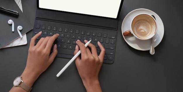 Vue de dessus de femme d'affaires travaillant sur son projet avec tablette numérique dans un lieu de travail moderne sombre