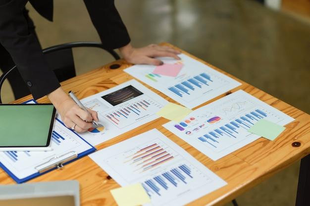 Vue de dessus d'une femme d'affaires vérifiant le rapport financier gérant le plan financier avec des documents